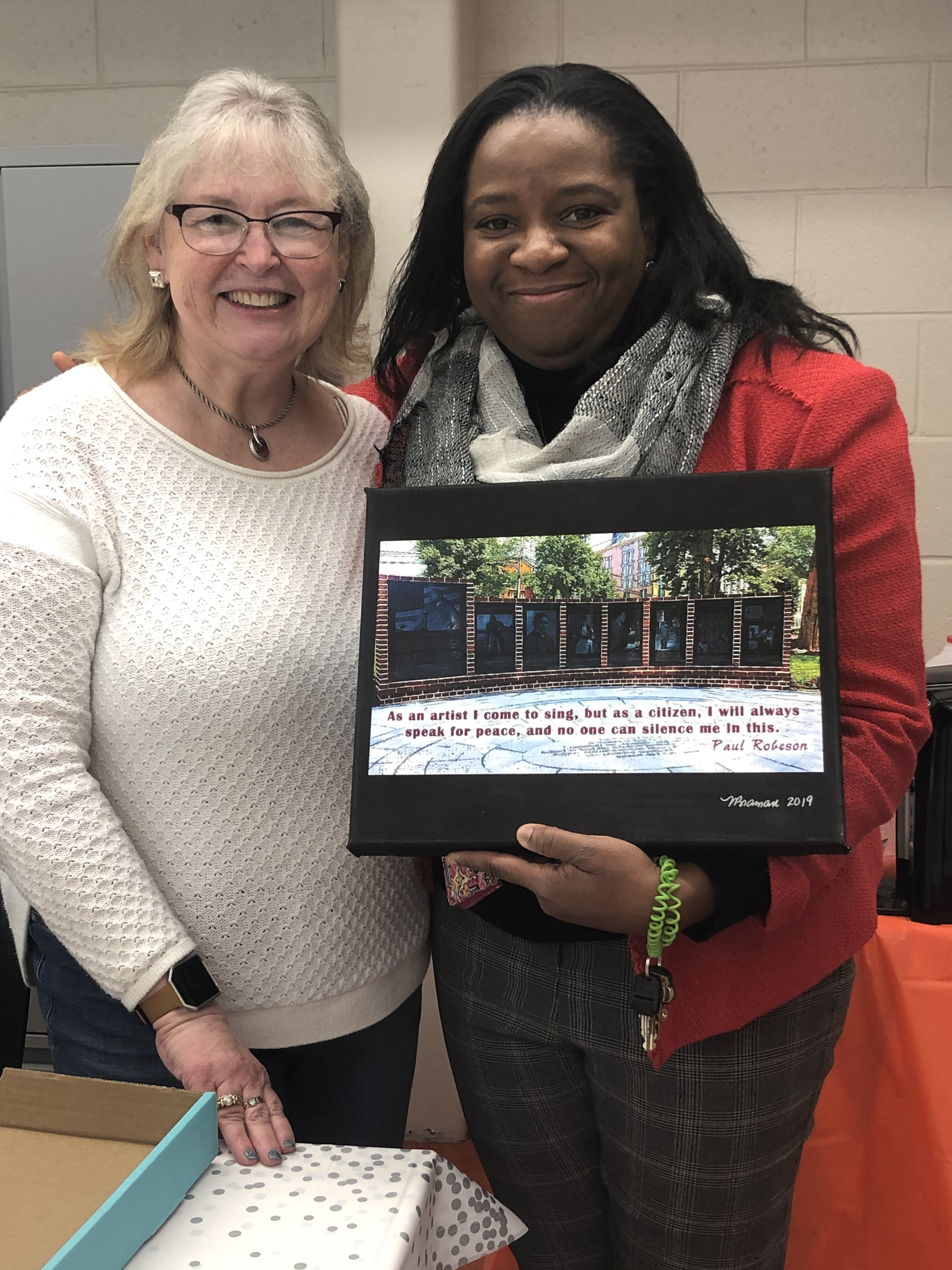 Noreen Braman presents a digital art photo to the principal of the Paul Robeson Community School for the Arts